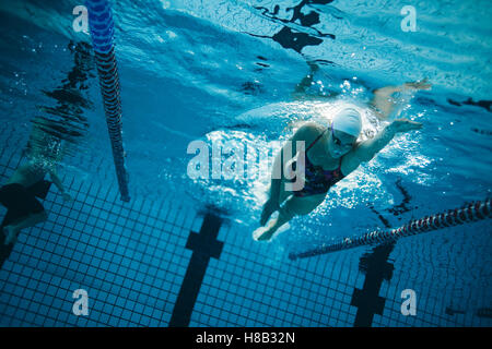 Riprese subacquee di giovani femmine nuotatore nuoto in piscina. Giovani femmine nuotatore formazione in piscina. Foto Stock