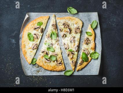 In casa la pizza a fungo con basilico tagliato a fettine su carta da forno sulla pietra nera di sfondo, vista dall'alto, Foto Stock