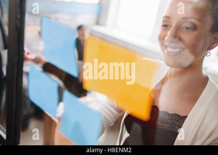 Sorridente giovane donna business sticking note adesive sulla parete di vetro. Mettere idee sulla parete di vetro. Foto Stock