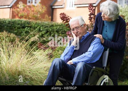 Premuto Senior uomo in carrozzella essendo spinto dalla moglie Foto Stock