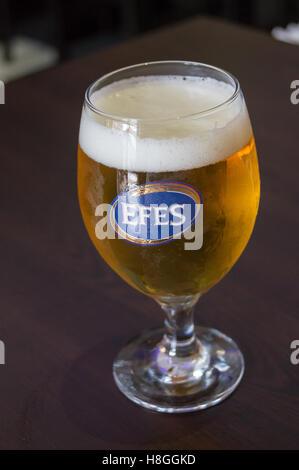 Un vetro stampato di Efes birra turco su un tavolo in un ristorante bar a Londra, Inghilterra, pub tavola bicchieri Foto Stock