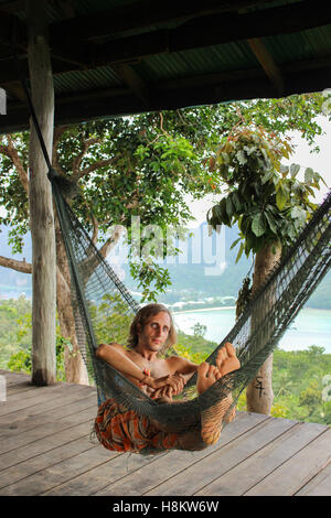 Casual uomo felice relax su una amaca in spiaggia vacanze Foto Stock