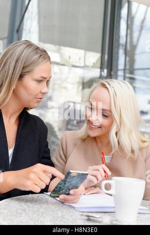 Giovani donne tramite telefono cellulare al cafe esterno Foto Stock