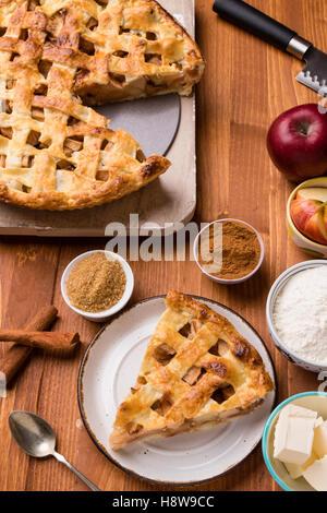 Freschi di forno fetta di torta di mele sul tavolo rustico impostazione con ingredienti Foto Stock