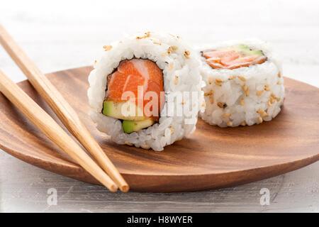 Due salmone fresco e avocado uramaki sushi servita su un piatto di legno con uno in posizione verticale per mostrare gli ingredienti Foto Stock
