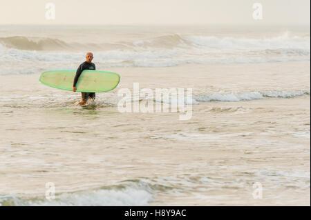 Surfer lasciando l'acqua dopo un sunrise 'dawn patrol' sessione di surf in spiaggia di Jacksonville, Florida, Stati Uniti d'America.