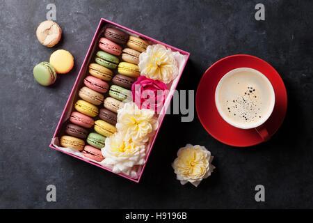 Colorato amaretti e caffè sul tavolo di pietra. Dolce macarons in confezione regalo e fiori. Vista superiore Foto Stock