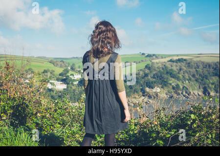 Una giovane donna in piedi sulla cima di una collina ed è ammirando il paesaggio Foto Stock
