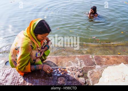 Donne accendendo candele per la puja e balneazione nel fiume Gange, Varanasi, India Foto Stock