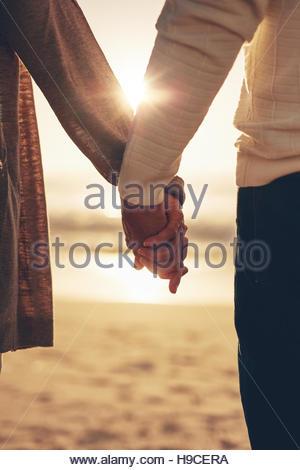 Vicino la vista posteriore di un romantico di coppia senior tenendo le mani contro il mare al tramonto. Foto Stock