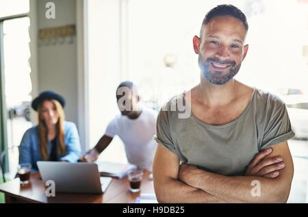 Casual cercando maschio in posa con mani incrociate su sfondo sfocato di co-lavoratori seduta a tavola in ufficio. Foto Stock