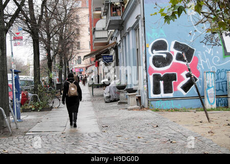 Vista posteriore della donna che cammina da una parete con graffiti indossando uno zaino in Prenzlauer Berg street Foto Stock