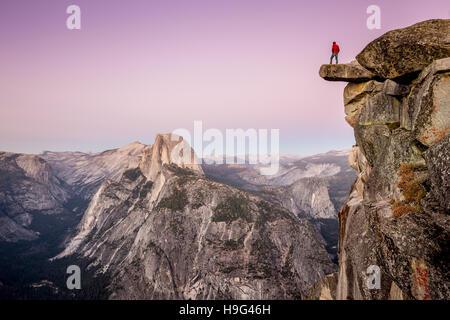 Un intrepido escursionista è in piedi sulla roccia a strapiombo presso il Glacier Point godendo della vista sulla mezza cupola al tramonto, Yosemite National Park, California, Stati Uniti d'America