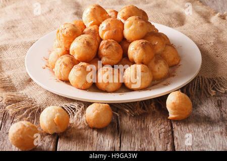 Piccole ciambelle con miele e cannella vicino sul tavolo orizzontale.