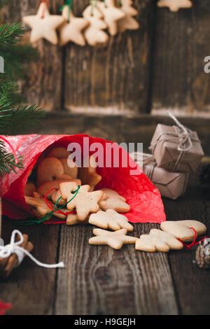 In casa biscotti natalizi sul tavolo rustico. I preparativi per le festività, manufatti artigianali e le decorazioni Foto Stock