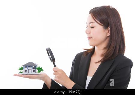 Donna di carriera di ispezionare una casa con lente di ingrandimento. Immobiliare di concetto. Foto Stock