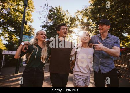 Quattro amici passeggiando nel parco di divertimenti. Un gruppo di giovani a piedi attraverso il parco dei divertimenti.