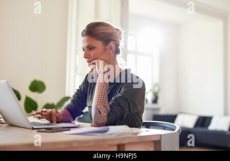 Ritratto di giovane e bella donna seduta presso l'ufficio domestico tramite computer portatile. Donne in cerca di Foto Stock