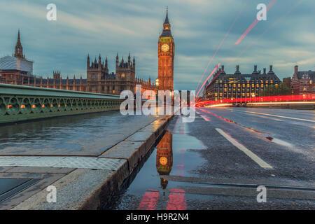 Una riflessione del Big Ben in una pozza sul Westminster Bridge al tramonto. Foto Stock