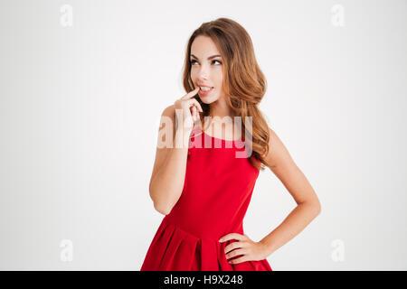 Ritratto di una donna pensosa in santa claus panno guardando lontano isolati su sfondo bianco Foto Stock