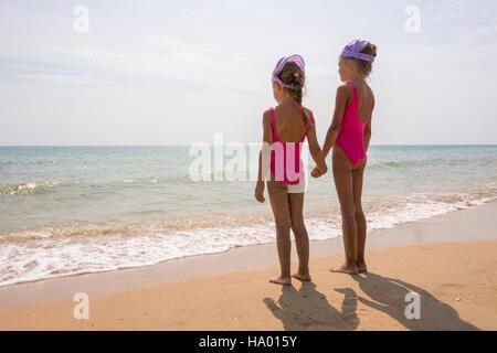 Due ragazze in costumi da bagno permanente sulla spiaggia e guardare l'orizzonte Foto Stock
