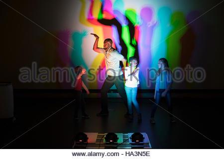 Scienziato e bambini multicolore di colata ombre su schermo di proiezione in science centre teatro Foto Stock
