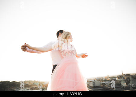 Coppia giovane in amore in posa sul tetto con perfetta vista città tenendo le mani e abbracciando . Bel tramonto Foto Stock
