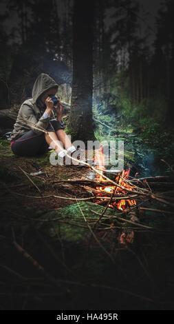 Giovane donna di bere il tè caldo dal fuoco della foresta Foto Stock