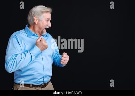 ... Positivo in grigio con capelli uomo barbuto in piedi su sfondo nero  Foto Stock 064e0ac970ed