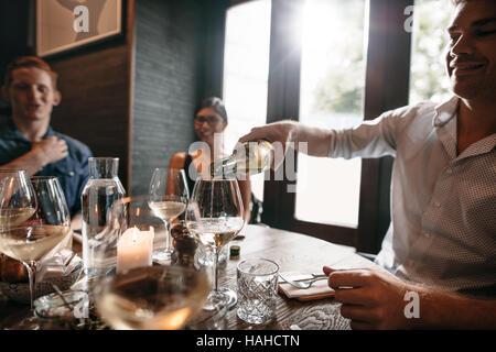 Gruppo di amici gustando un pasto con il vino al ristorante. Felice giovane versando il vino in bicchieri. Foto Stock