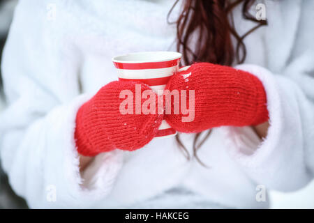 Mani in rosso mittens holding calda tazza di inverno con vapore Foto Stock
