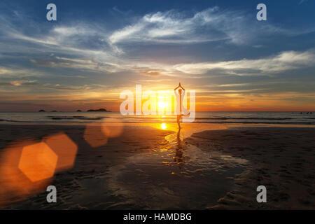 Piccole silhouette di donna a praticare yoga sulla spiaggia del mare durante il tramonto da favola. Foto Stock