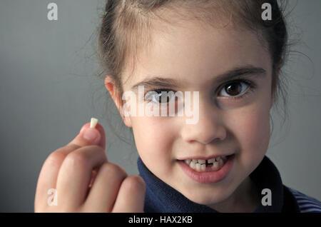 Orgogliosa ragazza giovane età (6) mantiene la sua prima caduta di denti di latte, guarda la telecamera. Infanzia Foto Stock