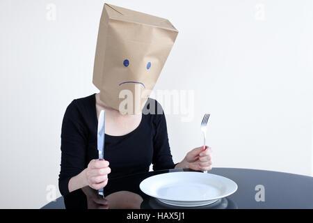 Anonimo triste donna con vuoto plat sedersi al tavolo da soli. Unica donna lifestyle, tristezza il concetto di spazio Foto Stock