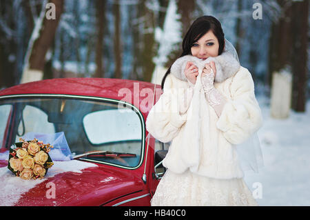 Sposa in inverno vicino alla vecchia auto d'epoca Foto Stock