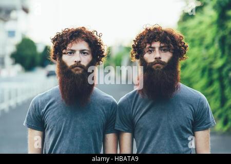 Ritratto di identico maschio adulto gemelli con i capelli rossi e le barbe sul marciapiede Foto Stock
