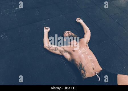 Esaurito maschio cross trainer sdraiato sul pavimento della palestra Foto Stock
