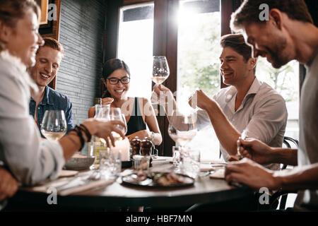 Giovane uomo alzando il bicchiere di vino con gli amici presso il ristorante. I giovani di gustare la cena in una Foto Stock