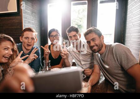 Multirazziale persone divertirsi presso il cafe prendendo un selfie con il telefono cellulare. Un gruppo di giovani amici seduti al ristorante tenendo autoritratto con smart Foto Stock