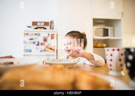 Poco ragazza seduta a tavola a mangiare la prima colazione Foto Stock
