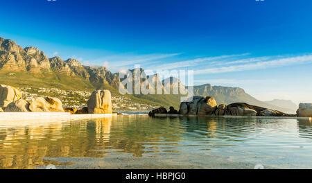 Camps Bay Ocean pool al tramonto con la città e le montagne alle spalle Foto Stock