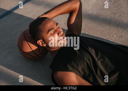 Closr su ritratto di uno stanco afro american sports uomo appoggiato su una palla da basket presso il parco giochi Foto Stock
