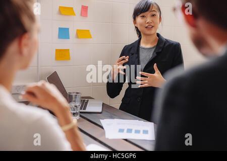 Imprenditrice in piedi da una parete con note adesive che conduce una presentazione aziendale. Executive femmina Foto Stock