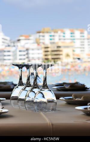 Ristorante sul mare con la tabella set. Bicchieri di cristallo vicino. L'immagine verticale. Foto Stock