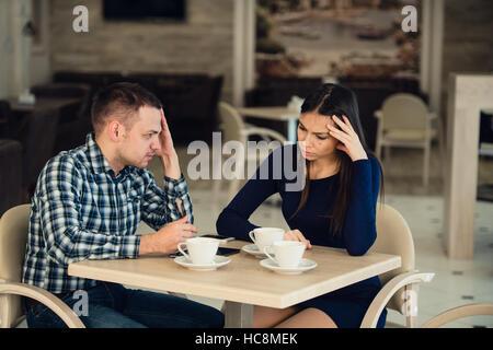 Coppia giovane sostenendo in una caffetteria. Lei ne ha avuto abbastanza, ragazzo è importante scusarsi. Problemi Foto Stock