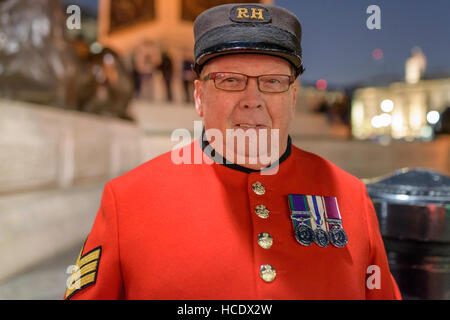 Chelsea titolare di pensione o di rendita che indossa il suo caratteristico mantello scarlatto a Trafalgar Square Foto Stock