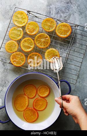 Femmina mettendo mano una fetta di arancia candita su una griglia ad asciugare.vista superiore Foto Stock