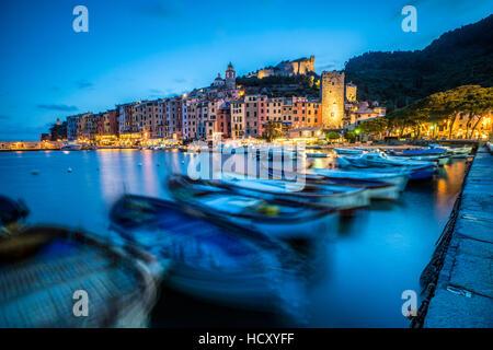 Vista del mare blu e le barche che circonda il colorato villaggio al tramonto, Portovenere, UNESCO, provincia della Foto Stock