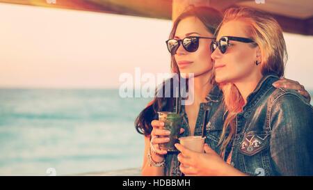 Ritratto di due belle ragazze trascorrere il tempo libero in outdoor cafe, bevendo cocktail gustosi e gode di splendida Foto Stock