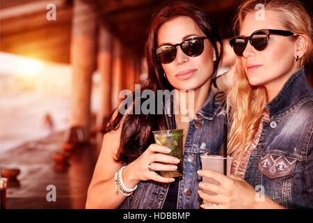Due donne bellissime con bevande rinfrescanti per divertirsi in spiaggia Cafe, elegante da indossare occhiali da Foto Stock